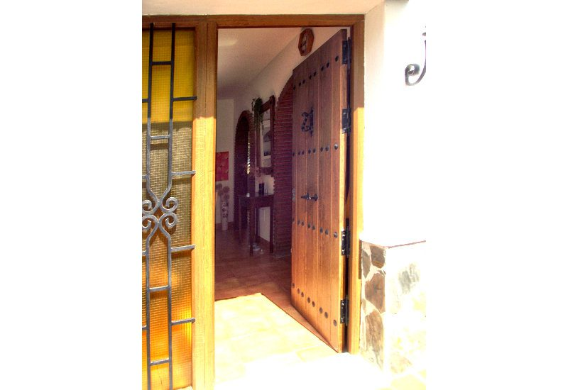 The wooden door of the entrance is rustical a broad